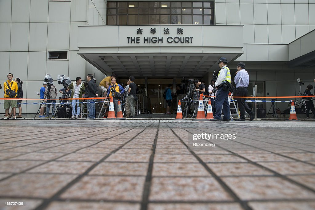 Members of the media stand waiting outside the High Court in Hong Kong, China, on Thursday, May 8, 2014. Thomas and Raymond Kwok, the billionaire brothers running Hong Kongs second-largest developer, are set to go on trial today for bribing Rafael Hui, the Chinese citys former No. 2 official. All three men have pleaded not guilty and denied all charges. Photographer: Brent Lewin/Bloomberg via Getty Images