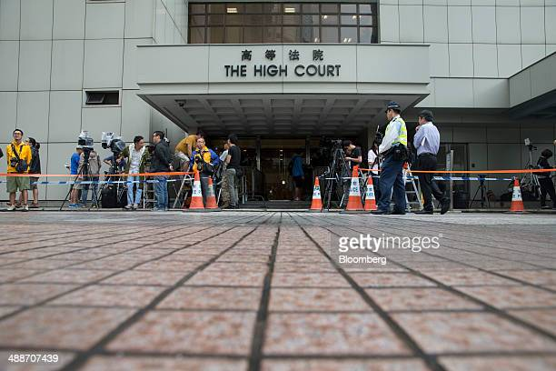 Members of the media stand waiting outside the High Court in Hong Kong China on Thursday May 8 2014 Thomas and Raymond Kwok the billionaire brothers...