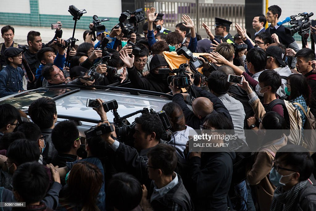Members of the media surround a car as supporters (top C) help escort a protester (not visible), who is facing one count of taking part in a riot on February 9 in the district of Mongkok, to the vehicle after a court hearing in Hong Kong on February 11, 2016. More than 30 people were expected to appear in court charged with rioting after clashes erupted in the city over official attempts to remove illegal street hawkers during the Lunar New Year. AFP PHOTO / DALE DE LA REY / AFP / DALE de la REY