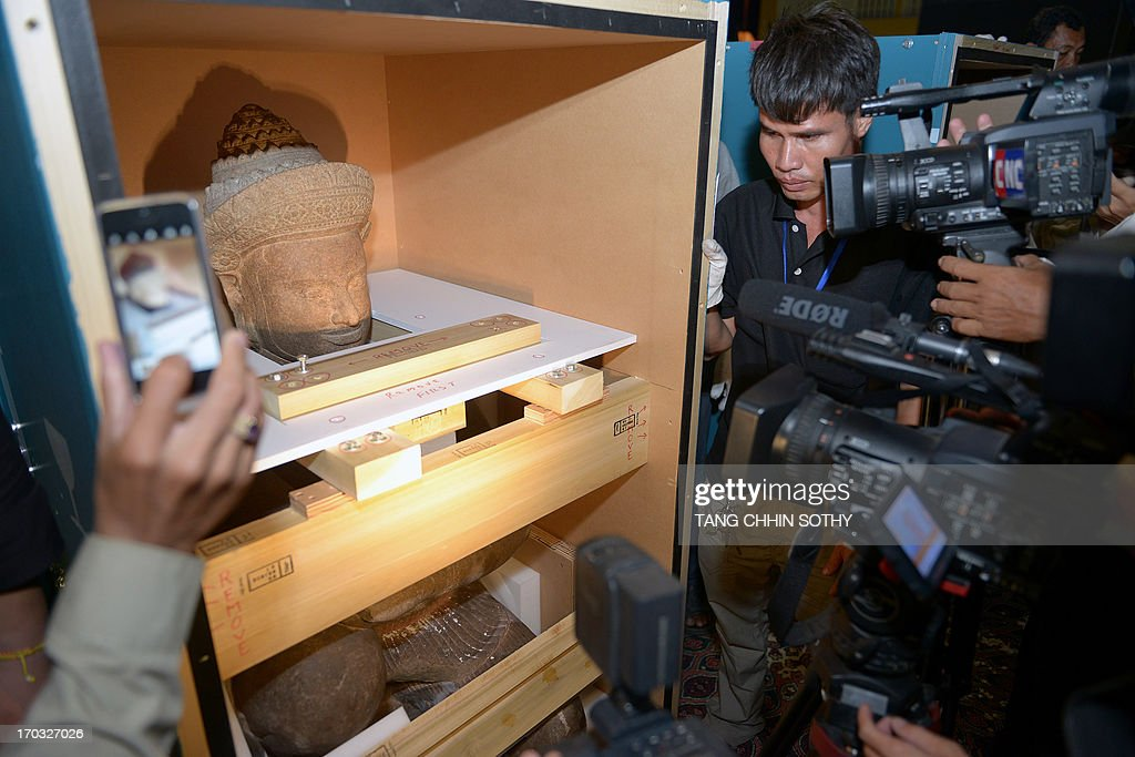 Members of the media surround a statue upon its arrival at Phnom Penh International Airport on June 11, 2013. Two 10th century statues that Cambodia says were looted from a jungle temple several decades ago were returned home on June 11 from New York's Metropolitan Museum of Art, in what the kingdom described as a 'historic' moment. AFP PHOTO/ TANG CHHIN SOTHY