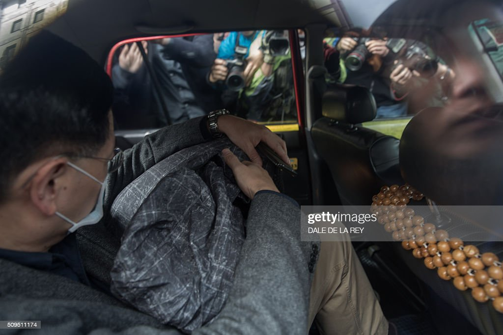 Members of the media surround a taxi as a supporter (L) helps escort a protester (covered with a grey jacket), who is facing one count of taking part in a riot on February 9 in the district of Mongkok, into the vehicle to leave after a court hearing in Hong Kong on February 11, 2016. More than 30 people were expected to appear in court charged with rioting after clashes erupted in the city over official attempts to remove illegal street hawkers during the Lunar New Year. AFP PHOTO / DALE DE LA REY / AFP / DALE de la REY