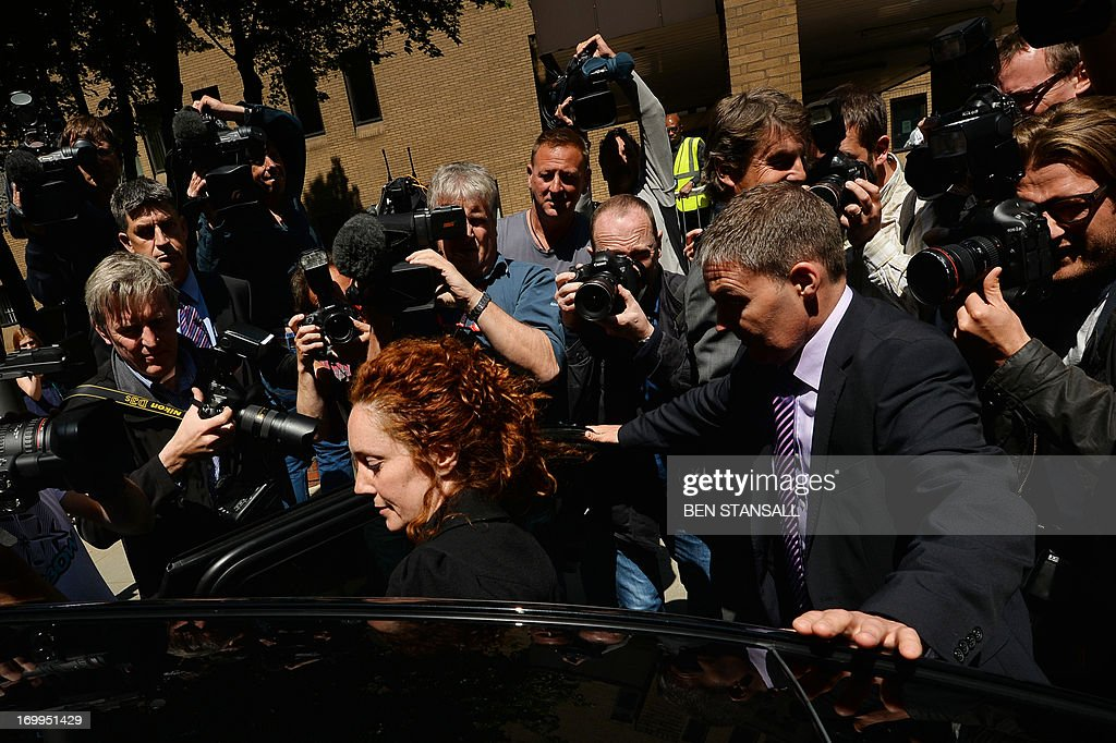 Members of the media surround former News International chief executive Rebekah Brooks (C) as she gets into a car to leave Southwark Crown Court in London on June 5, 2013 after attending a hearing into charges linked to the phone-hacking scandal. Rebekah Brooks, former chief executive of Rupert Murdoch's British newspaper wing News International, pleaded not guilty on June 5 to charges linked to the phone-hacking scandal that brought down his News of the World tabloid. Brooks, 45, denied five charges including conspiracy to hack phones, conspiracy to commit misconduct in a public office and conspiracy to pervert the course of justice. She appeared in a packed courtroom in London alongside several other former News International staff and her husband Charlie Brooks, who are also accused of conspiring to pervert the course of justice by hiding evidence relating to the hacking scandal.