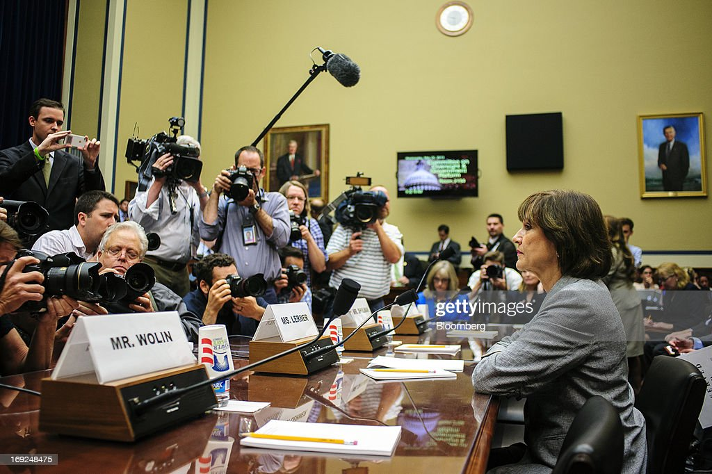 Members of the media surround Lois Lerner, the director of the Internal Revenue Service's (IRS) exempt organizations office, right, before the start of a House Oversight and Government Reform Committee hearing in Washington, D.C., U.S., on Wednesday, May 22, 2013. Lerner, the mid-level IRS official at the center of a controversy over treatment of small-government groups, invoked her right not to testify after reading a statement denying that she had committed any crimes. Photographer: Pete Marovich/Bloomberg via Getty Images