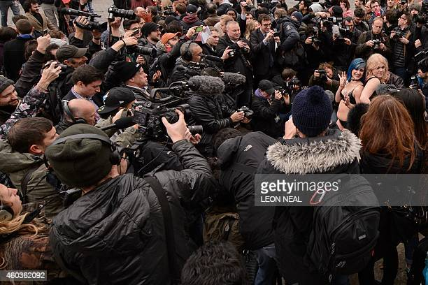 Members of the media surround two demonstrators as they prepare to take part in a mass 'facesitting protest' outside the Houses of Parliament in...