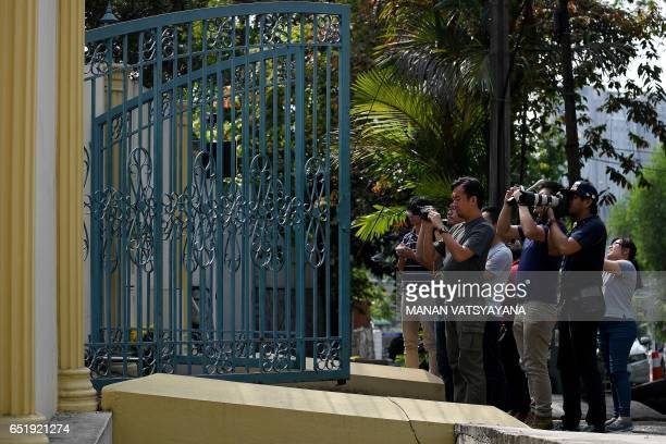 Members of the media take photographs after a car entered the compounds of the North Korean embassy in Kuala Lumpur on March 11 2017 Malaysia's...