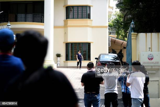 Members of the media take photographs of an unidentified woman leaving the North Korean embassy in Kuala Lumpur on March 17 2017 Malaysian...