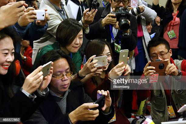 Members of the media take photographs of billionaire Lei Jun chairman and chief executive officer of Xiaomi Corp not seen during a news conference on...