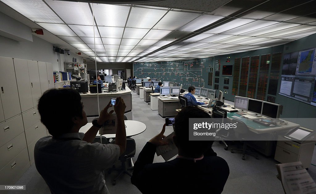 Members of the media take photographs of Tokyo Electric Power Co. (Tepco) employees working at the company's central grid management center in Tokyo, Japan, on Thursday, June 20, 2013. Tepco faces more than 11 trillion yen ($108 billion) in estimated costs, including compensation payments, after the quake and tsunami two years ago caused three meltdowns and radiation leaks, forcing about 160,000 people to evacuate. Photographer: Tomohiro Ohsumi/Bloomberg via Getty Images