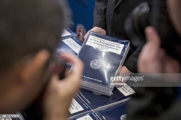 Members of the media take photographs of US President Donald Trump's fiscal 2018 budget proposal on display in the Senate Budget Committee hearing...