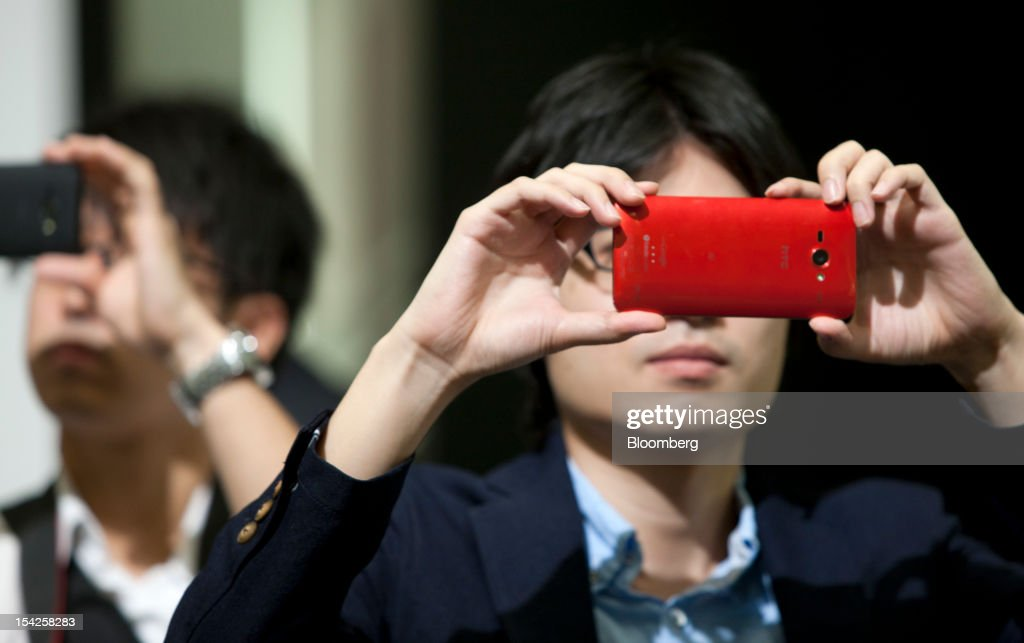 Members of the media take photographs using HTC Corp. HTC J smartphones for KDDI Corp. at the unveiling of KDDI's new smartphone line-up in Tokyo, Japan, on Wednesday, Oct. 17, 2012. KDDI is Japan's second-largest mobile-phone carrier. Photographer: Tomohiro Ohsumi/Bloomberg via Getty Images