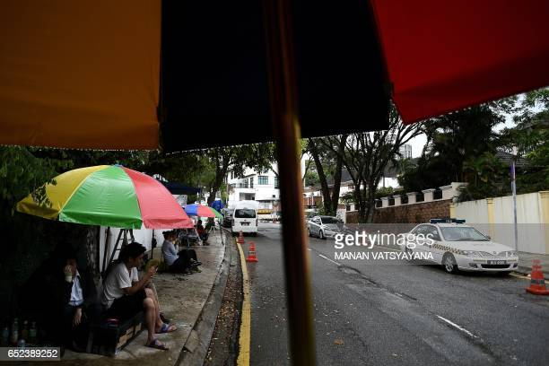 Members of the media take shelter from rain as a Malaysian Police car is seen parked outside the North Korean embassy in Kuala Lumpur on March 12...