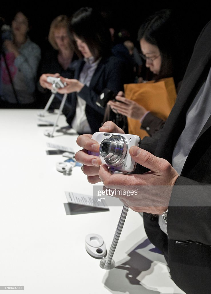 Members of the media test the new Samsung S4 Zoom phone, a new design featuring a phone and camera combination during the world launch of new Samsung Galaxy and Ativ products at Earls Court, London on June 20, 2013.