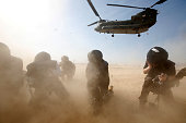 Members of the media try to protect themselves from dust blown up by a British forces transport helicopter as it lands at the forward operating base...