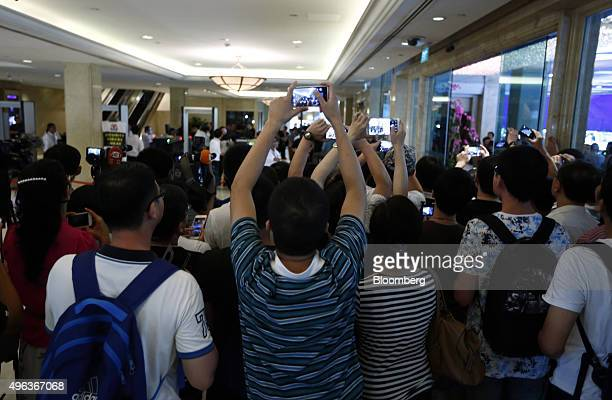 Members of the media use their smartphones to take photographs from outside a security inspection gate following a summit between Taiwanese President...