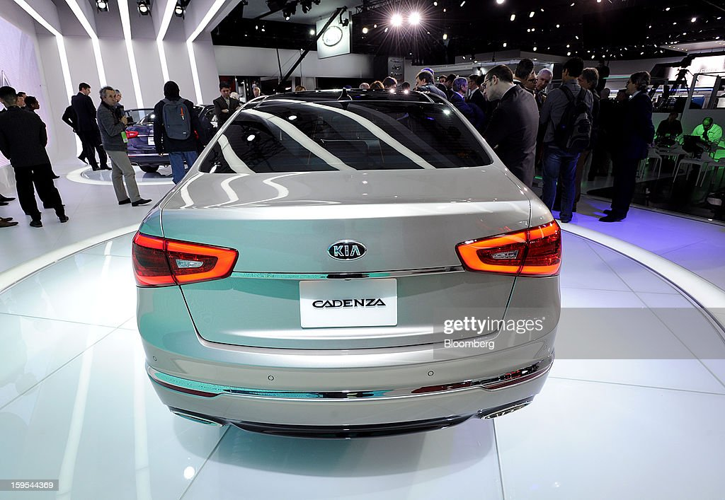 Members of the media view the Kia Motors Corp. Cadenza sedan after it is unveiled during the 2013 North American International Auto Show (NAIAS) in Detroit, Michigan, U.S., on Tuesday, Jan. 15, 2013. The Detroit auto show runs through Jan. 27 and will display over 500 vehicles, representing the most innovative designs in the world. Photographer: David Paul Morris/Bloomberg via Getty Images