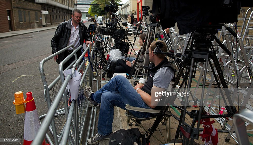 Members of the media wait in the media pen with ladders and tripods outside The Lindo Wing of Saint Mary's Hospital in Paddington, west London on July 4, 2013. Prince William and his wife Catherine's baby, which will be third in line to the throne, will be born in the private Lindo wing of St Mary's Hospital, where William was born in 1982 and his brother Harry in 1984. AFP PHOTO / ANDREW COWIE