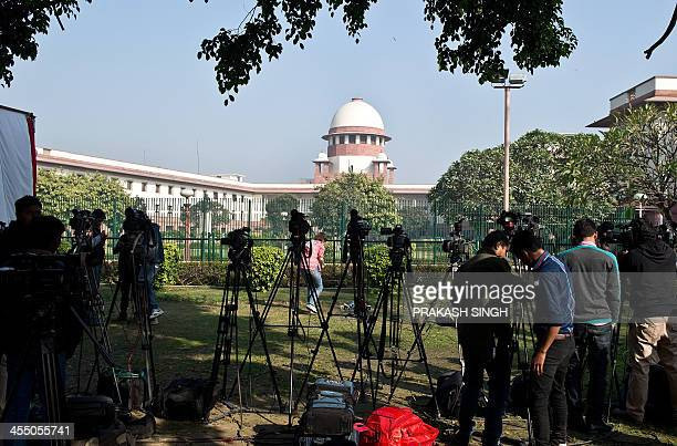 Members of the media wait on the Supreme Court lawn in New Delhi on December 11 2013 India's Supreme Court upheld a colonialera law criminalising...