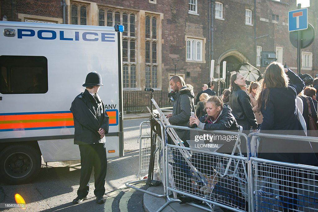 Members of the media wait opposite St James's Palace in central London on October 23, 2013, as Prince George of Cambridge is baptised inside Chapel Royal. Prince William and his wife Catherine gather close friends and family for the christening of their baby son Prince George, in a low-key ceremony far removed from the global hype surrounding their wedding. AFP PHOTO/LEON NEAL