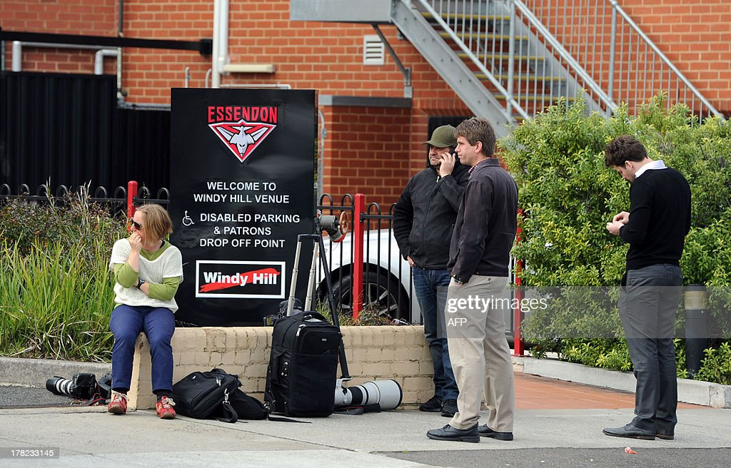 Members of the media wait outside Windy Hill, the Essendon Football Club's home ground in Melbourne, after the club accepted sanctions from the Australian Football League (AFL) on August 28, 2013. Banned Essendon coach James Hird on August 28 accepted some responsibility for a record fine slapped on the team and said it was now time to move on for the good of the game. The top AFL side was on August 27 hit with the biggest fine in the sport's history -- two million Australian dollars (1.8 million USD) -- and Hird was suspended for 12 months for bringing the game into disrepute. AFP PHOTO / Mal Fairclough