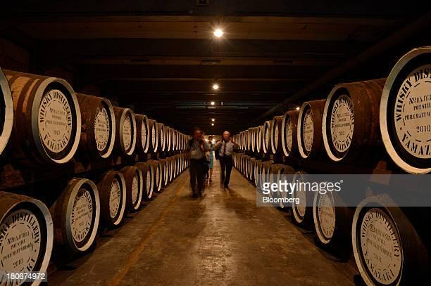 Members of the media walk past casks containing pot still pure malt whisky in a warehouse at Suntory Holdings Ltd's Yamazaki distillery in Shimamoto...