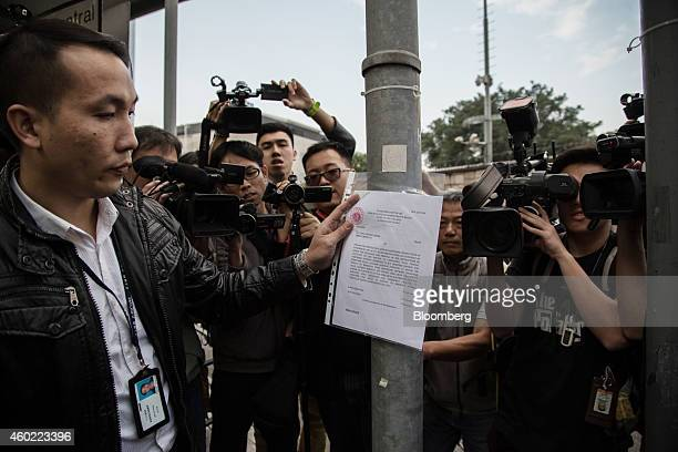 Members of the media watch a bailiff attach a copy of a court injunction to a lamppost near the Central Government Offices in the Admiralty district...