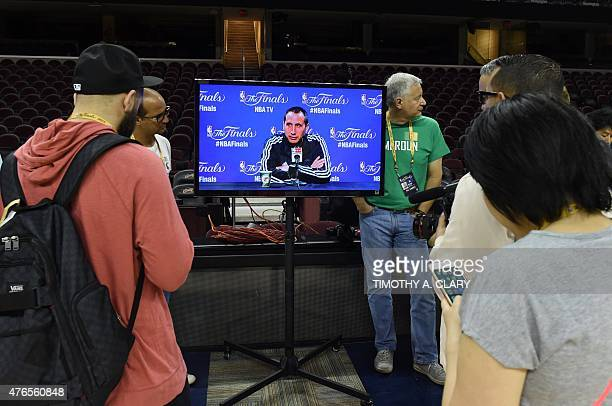 Members of the media watch Cleveland Cavaliers head coach David Blatt on a tv screen the day after their Game 3 win over Golden State Warriors at the...