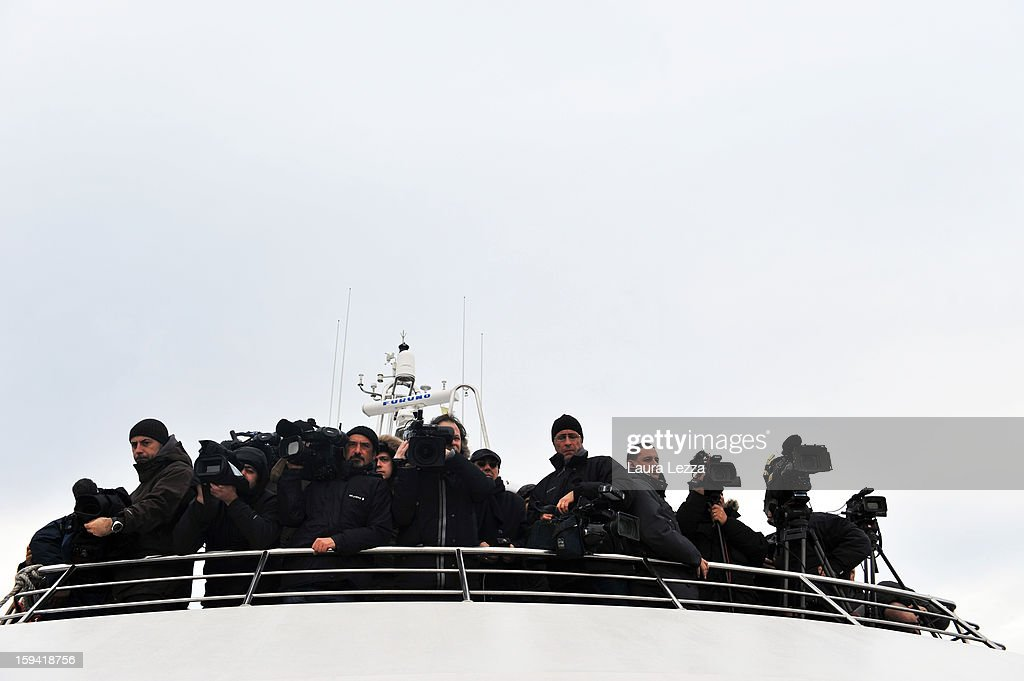 Members of the media watch from a boat during a minute of silence to mark the exact time the Costa Concordia crashed, on January 13, 2013 in Giglio Porto, Italy. A year after the sinking of the ship Costa Concordia, relatives of the victims, survivors, island residents, law enforcement and institutions gathered to mark the first anniversary and commemorate the dead. More than four thousand people were on board when the ship hit a rock off the Tuscan coast, killing 32 and leaving two people missing.