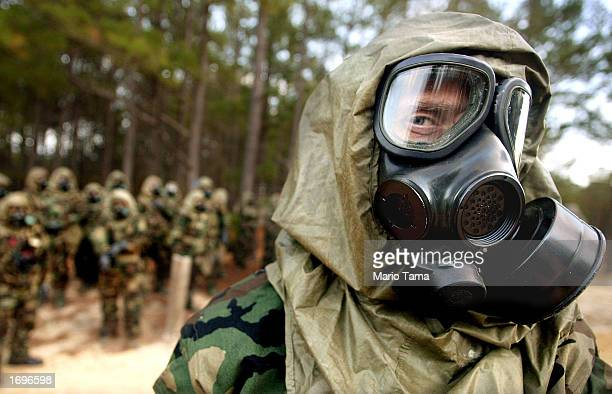 Members of the media wear chemical protection suits as they are trained to protect against nuclear chemical and biological attacks at the US Army...