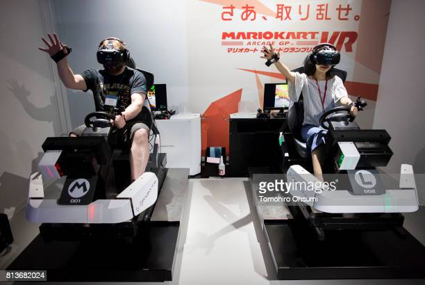 Members of the media wearing HTC Corp Vive virtual reality headsets try the Mario Kart Arcade GP VR attraction at the VR Zone Shinjuku theme park...