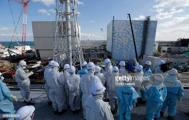 Members of the media wearing protective suits and masks receive a briefing from Tokyo Electric Power Co employees in front of the No 1 and No2...