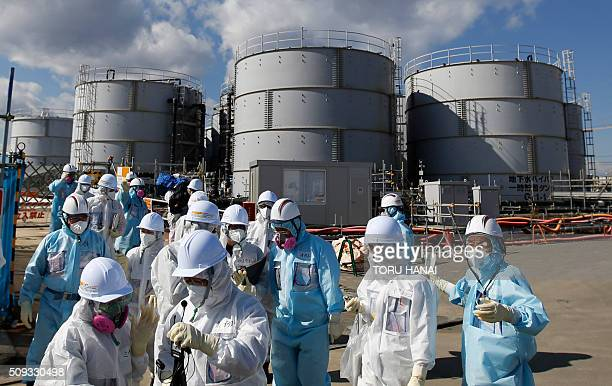 Members of the media wearing white protective suits and masks walk after they receive a briefing from Tokyo Electric Power Co employees in front of...
