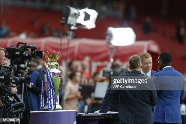 Members of the media work inside the stadium next to the Premier League trophy ahead of the English Premier League football match between Arsenal and...