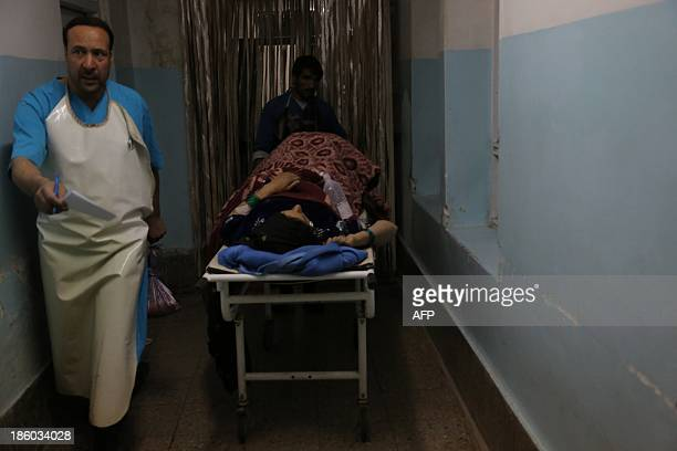 Members of the medical staff carry a victim of a roadside bomb at a hospital in the Andar district of the Ghazni province on October 27 2013 A...