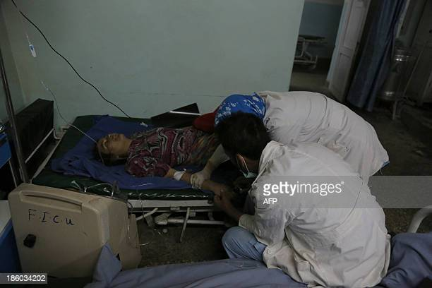 Members of the medical staff take care of a victim of a roadside bomb at a hospital in the Andar district of the Ghazni province on October 27 2013 A...