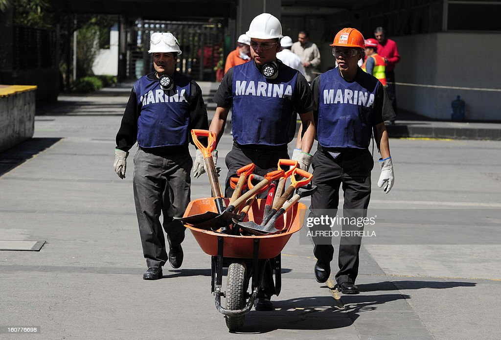 Members of the Mexican Navy arrive with spades to the damaged building of Mexican state-owned oil giant Pemex, after a blast, in Mexico City on February 5, 2013. A gas build-up caused the explosion that rocked the headquarters of Mexico's state-owned oil firm last week, killing 37 people, officials said Monday, ruling out a bomb attack. The explosion also injured morfe than 120 people. AFP PHOTO/Alredo Estrella