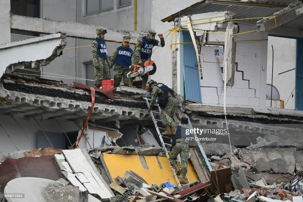 Members of the Mexican Navy search for survivors in a flattened building in Mexico City on September 21, 2017 two days after a strong quake hit central Mexico. A powerful 7.1 earthquake shook Mexico City on Tuesday, causing panic among the megalopolis' 20 million inhabitants on the 32nd anniversary of a devastating 1985 quake. / AFP PHOTO / Ronaldo SCHEMIDT