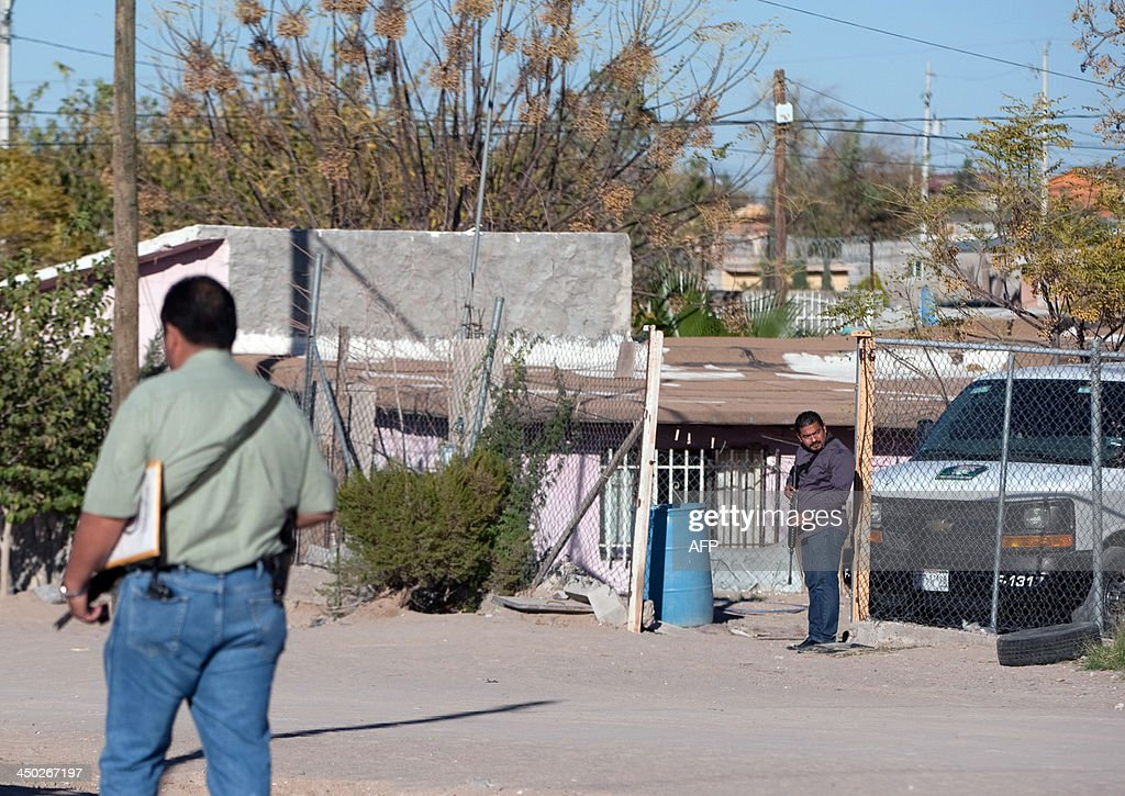 Members of the Mexican police stand guard at the entrance of a house in which eight members of a family were killed by gunmen in Ciudad Juarez Mexico...
