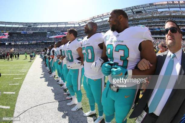 Members of the Miami Dolphins lock arms for the National Anthem before the game against the New York Jets on September 24 2017 at MetLife Stadium in...