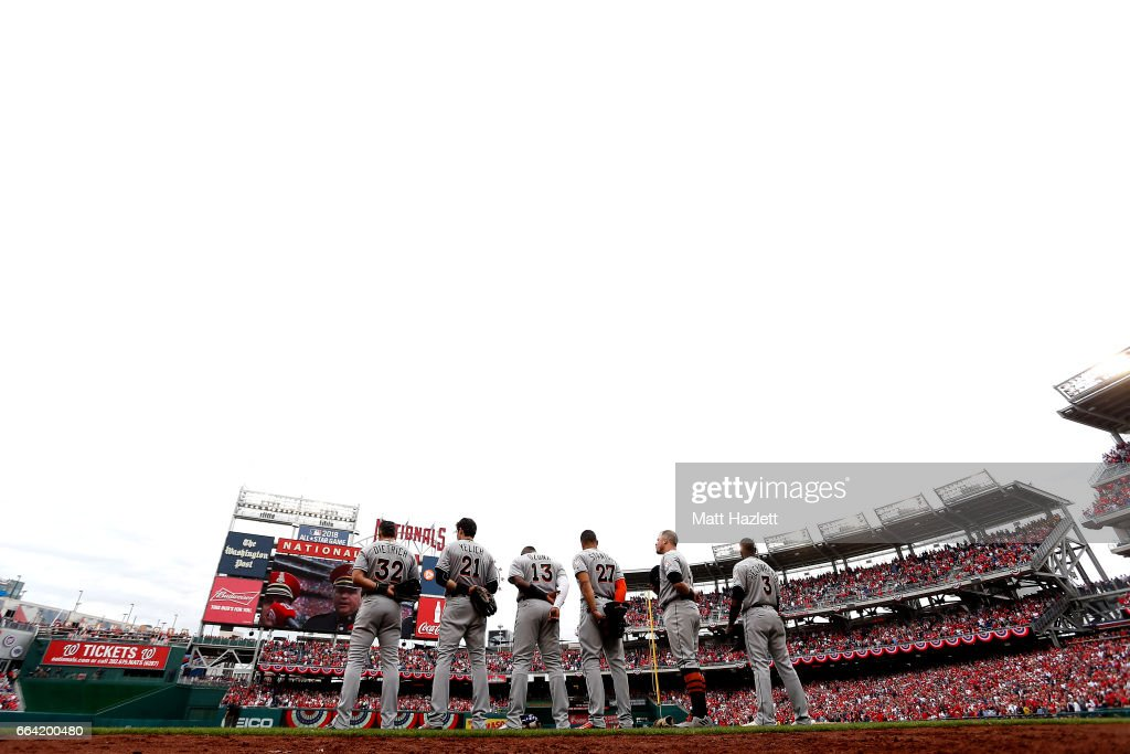 Members of the Miami Marlins stand for the playing of God Bless America during the opening day game against the Washington Nationals at Nationals Park on April 3, 2017 in Washington, DC.