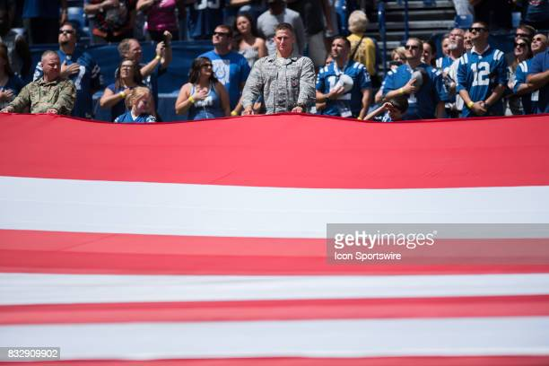 Members of the military hold the flag on the field before the NFL preseason game between the Detroit Lions and Indianapolis Colts on August 13 at...