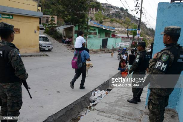 Members of the Military Police stand guard as a man takes his son to the Maximiliano Sagastume school in Sagastume a neighborhood on the north side...