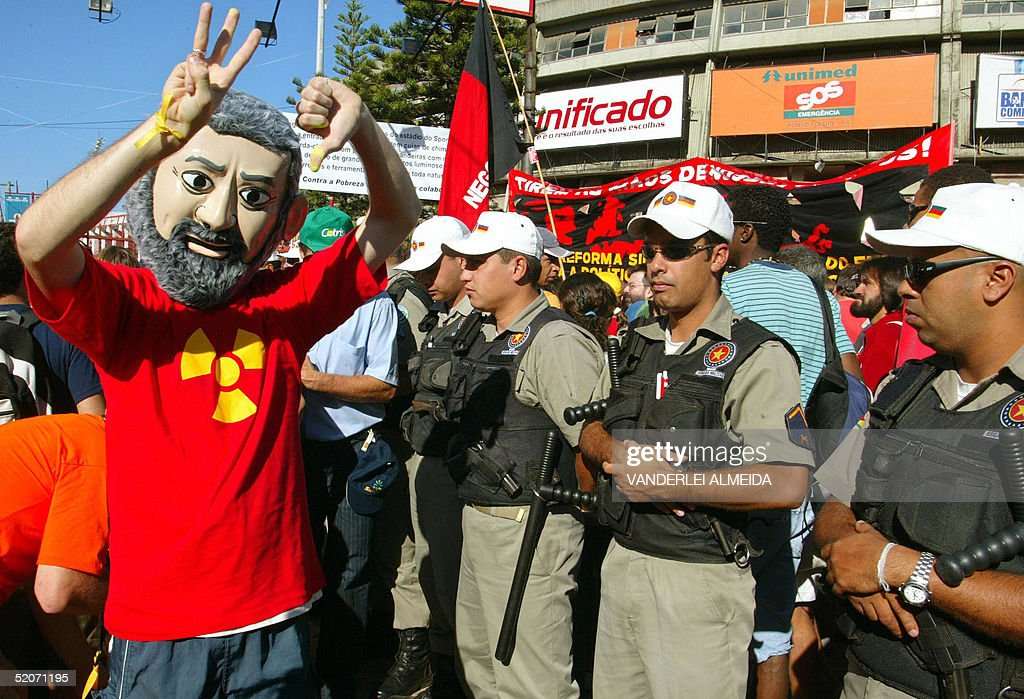 Members of the Military Police stand guard as an antiglobalization militant demonstrates against the Brazilian President Luiz Inacio Lula da Silva...