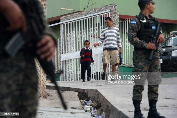 TOPSHOT Members of the Military Police stand guard as students arrive for class at the Maximiliano Sagastume school in Sagastume a neighborhood on...