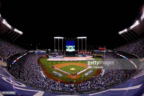 Members of the miltary hold a giant American flag before the start of Game One of the 2014 World Series between the Kansas City Royals and the San...