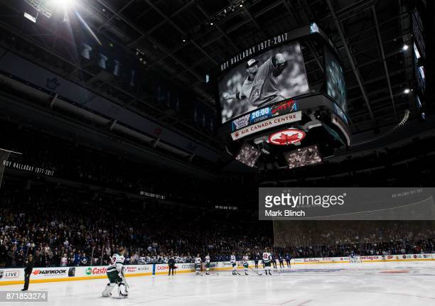 Members of the Minnesota Wild and the Toronto Maple Leafs stand during a moment of silence for former Toronto Blue Jays pitcher Roy Halladay whop was...