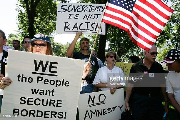Members of the Minuteman Project hold posters and US flag during an anti illegalimmigrant rally at the Upper Senate Park May 12 2006 on Capitol Hill...