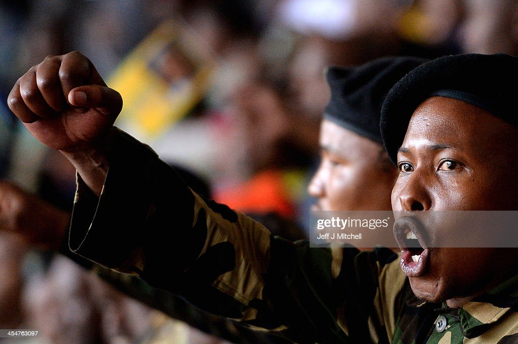 Members of the MK sing and dance during the Nelson Mandela memorial service at the FNB Stadium, on December 10, 2013 in Johannesburg, South Africa. Over 60 heads of state have travelled to South Africa to attend a week of events commemorating the life of former South African President Nelson Mandela. Mr. Mandela passed away on the evening of December 5, 2013 at his home in Houghton at the age of 95. Mandela became South Africa's first black president in 1994 after spending 27 years in jail for his activism against apartheid in a racially-divided South Africa.