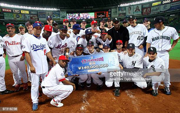 Members of the MLB AllStars hold a check for 140 million yen after winning Game 5 53 and sweeping the fivegame series against the Nippon Professional...