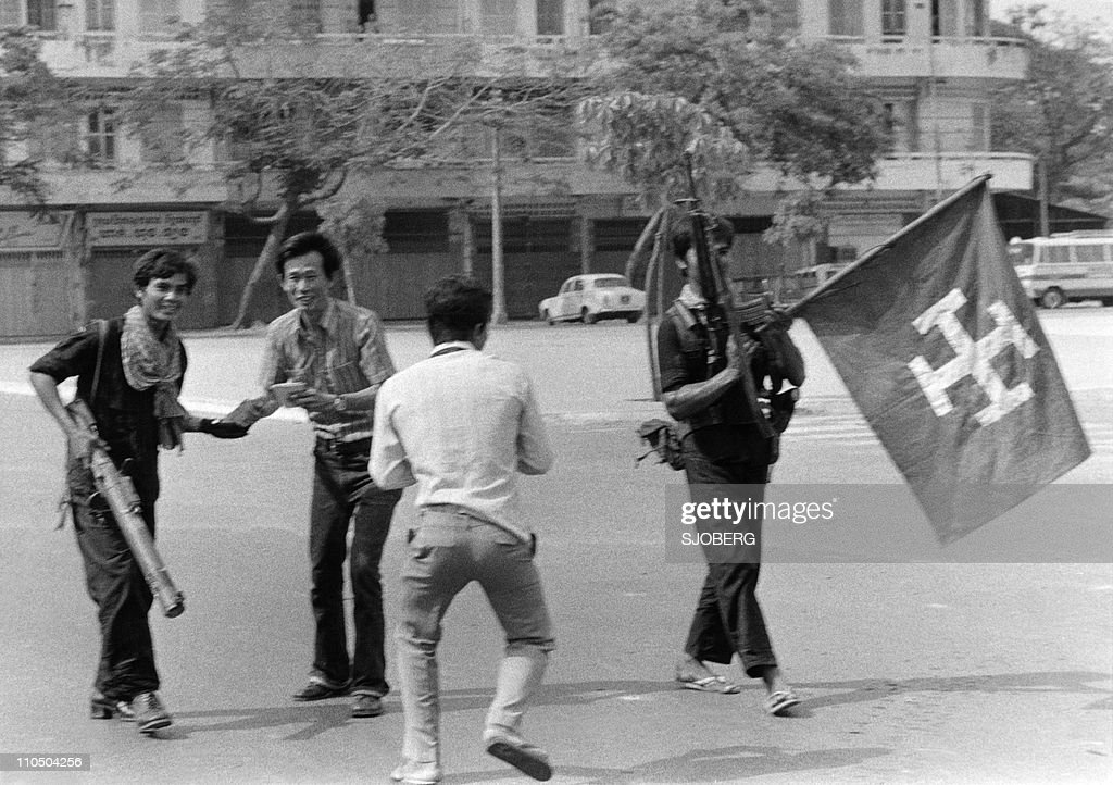 Members of the MONATIO (Mouvement National) group brandishing their flag are greeted are greeted by jubilant youngsters as they walk the streets in Phnom Penh 17 April 1975. On New Year's Day 1975, Communist troops led by Pol Pot and Ieng Sary, launched an offensive to oust Lon Nol's Khmer Republic. The Lon Nol governement in Phom Penh surrendered 17 April 1975 after 117 days of the hardest fighting of the war. Immediately after its victory, the PCK ordered the evacuation of all cities and towns. Many of the foreigners and some Cambodians, who couldn't or wouldn't flee Cambodia, took refuge at the embassy from which they were taken by truck to Thailand two weeks later. The Mouvement National (MONATIO) was a small political faction which welcomed the Khmer Rouge upon their arrival in Phnom Penh and were later quickly eliminated. AFP PHOTO