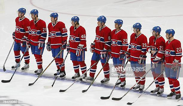 Members of the Montreal Canadiens stand for the national anthem before play against the Detroit Red Wings during their NHL game at the Bell Centre on...